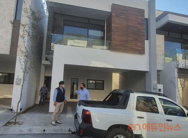 멕시코 에이전트와 한 주택앞에서 만나 이야기를 나누는 남편.(사진=선우림)